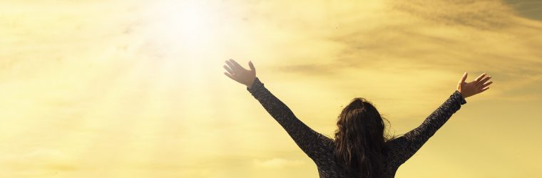 arms outstretched to sun in yellow sky