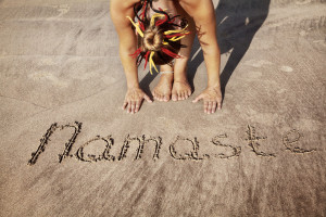 24399238 - woman doing yoga on the beach near namaste handwriting in goa, india